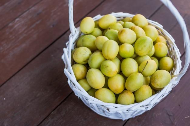 Prunes mûres juteuses colorées jaunes et vertes dans un panier en osier.