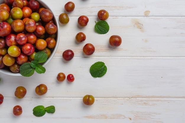 Prunes mûres sur la surface en bois blanche.