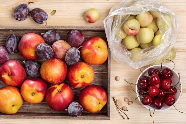 Prunes et nectarines en boîte, vue du dessus. ensemble de fruits frais.
