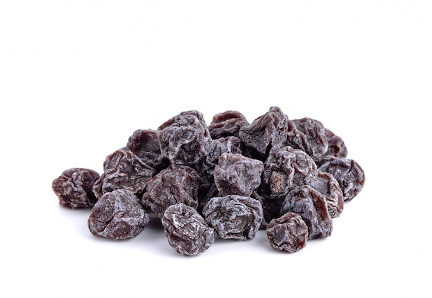 Prunes noires douces séchées isolés sur blanc