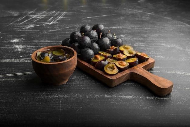 Prunes noires entières et tranchées sur une planche de bois, vue d'angle