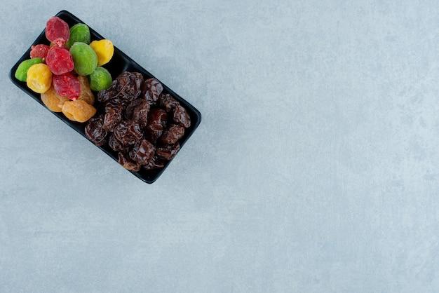Prunes noires séchées et cerises multicolores sur un plateau. photo de haute qualité