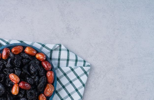 Prunes noires sèches et dattes dans un plateau bleu.