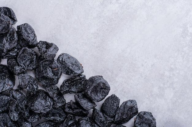 Prunes noires sèches isolées sur une surface en béton