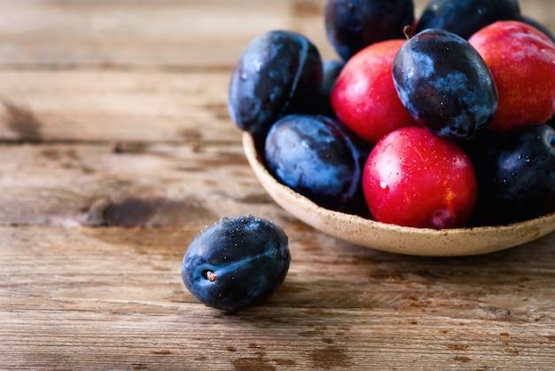 Prunes organiques bleues et roses sur bois sombre.