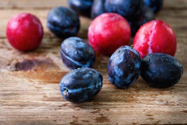 Et prunes organiques roses sur bois foncé.