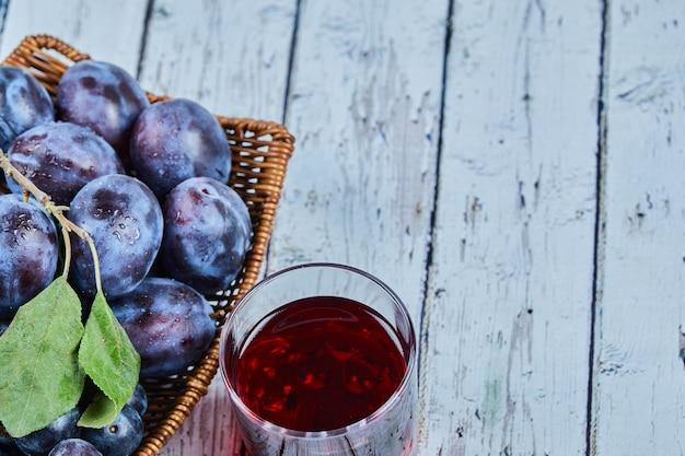 Prunes sur panier sur bleu avec un verre de jus.