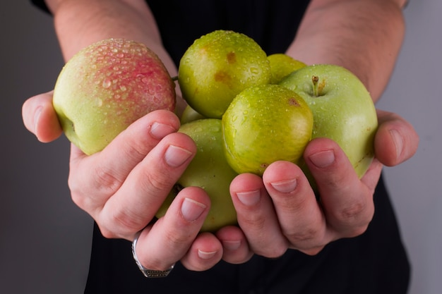 Prunes et pommes cerises vertes entre les mains d'une personne