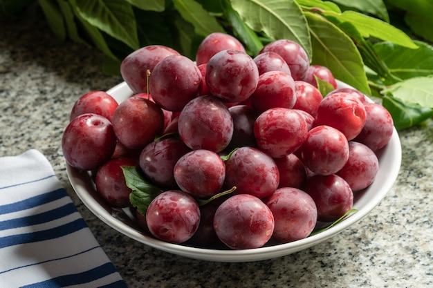 Prunes rouges biologiques fraîches dans un bol