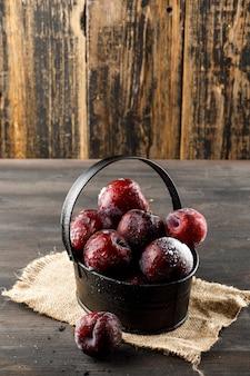 Prunes rouges dans un panier avec morceau de sac vue grand angle sur la surface en bois et grungy