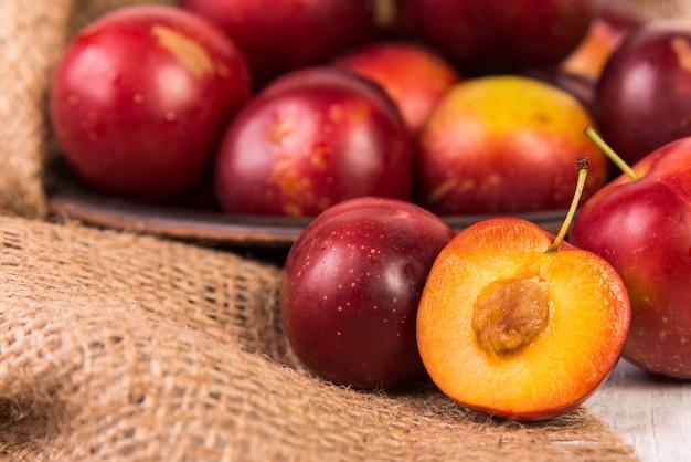 Prunes rouges mûres sur sac de jute