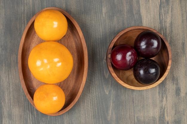 Prunes savoureuses avec de délicieuses mandarines sur une plaque en bois