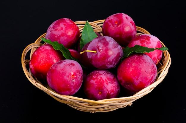 Prunes sucrées mûres dans un bol en osier. photo