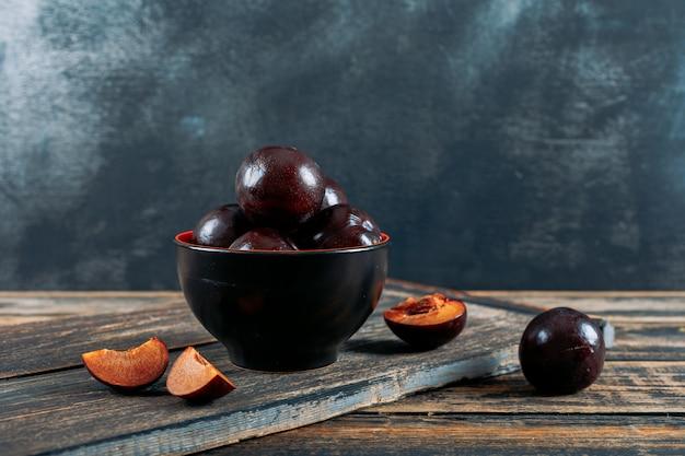 Prunes avec des tranches dans un bol avec vue de côté de planche de bois sur un fond grunge en bois foncé et gris