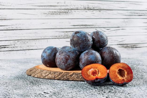 Prunes en tranches fraîches dans une planche de bois sur fond de stuc gris, vue latérale.