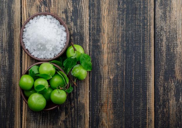 Prunes vertes dans une assiette en argile avec du sel dans un bol et feuilles vue de dessus sur un mur en bois