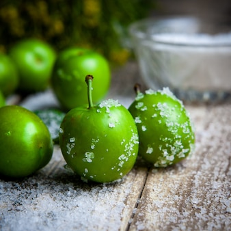 Prunes vertes avec du sel, vue latérale des plantes sur une table en bois