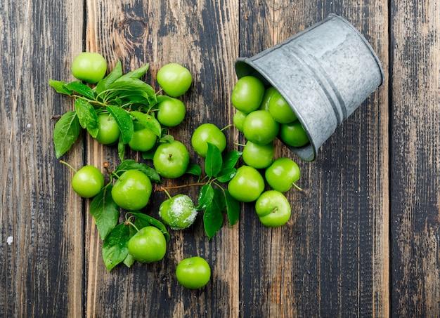 Prunes vertes éparses avec des feuilles, du sel dans un mini seau sur mur en bois, vue de dessus.