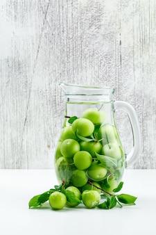 Prunes vertes avec des feuilles dans un pot en verre sur un mur blanc et grungy, vue latérale.