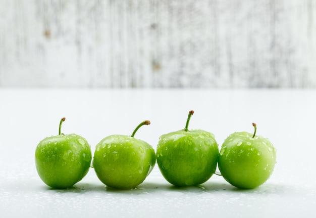 Prunes vertes fraîches sur mur blanc et grungy. vue de côté.