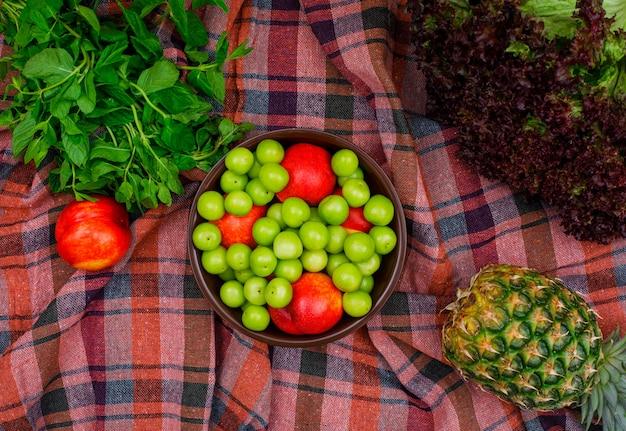 Prunes vertes et pêches dans un bol en argile avec des feuilles vertes, un plat d'ananas et de laitue posé sur un tissu de pique-nique