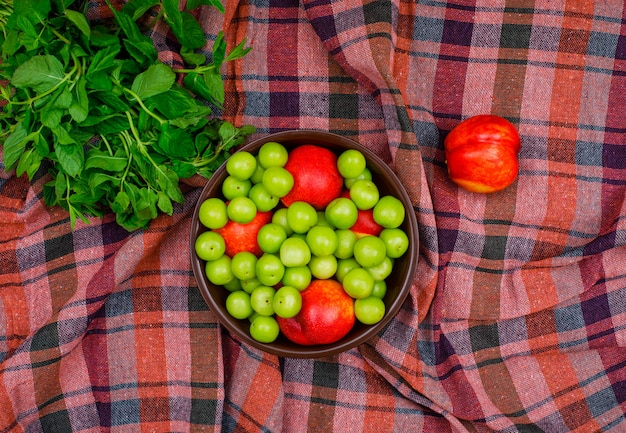 Prunes vertes et pêches dans un bol en argile avec des feuilles vertes à plat sur un tissu de pique-nique