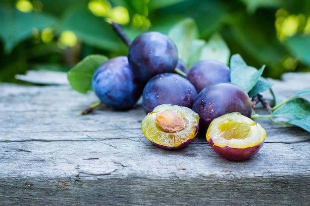 Prunes violettes sur le fond en bois rustique dans le jardin. espace de copie. fruits de récolte d'été ou d'automne