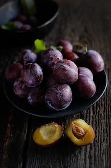 Prunes violettes fraîches sur fond de table en bois foncé