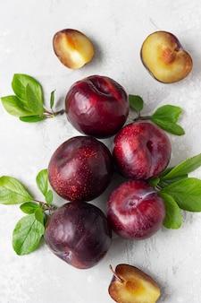 Prunes violettes juteuses mûres, entières et en tranches, avec des feuilles.