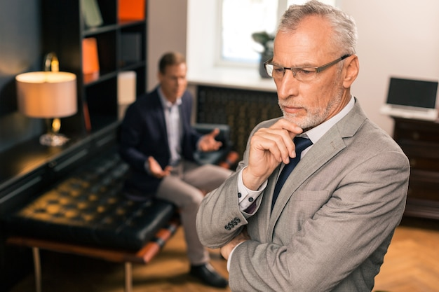 Psychanalyste aux cheveux gris pensif sérieux debout dans son bureau et pensant tout en soutenant son menton