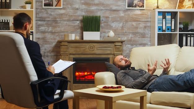 Psychanalyste donnant des consultations à un jeune homme au sujet de ses problèmes relationnels.