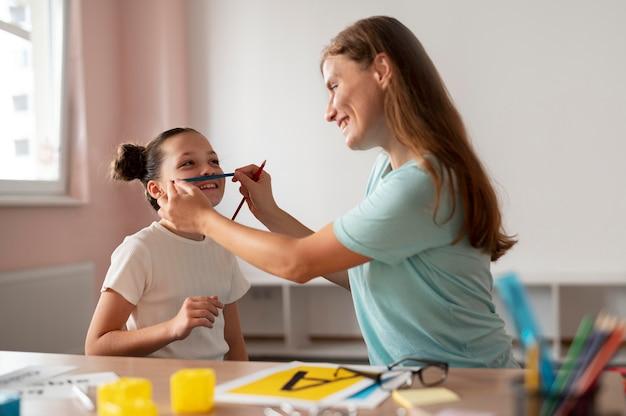 Psychologue aidant une petite fille en orthophonie à l'intérieur