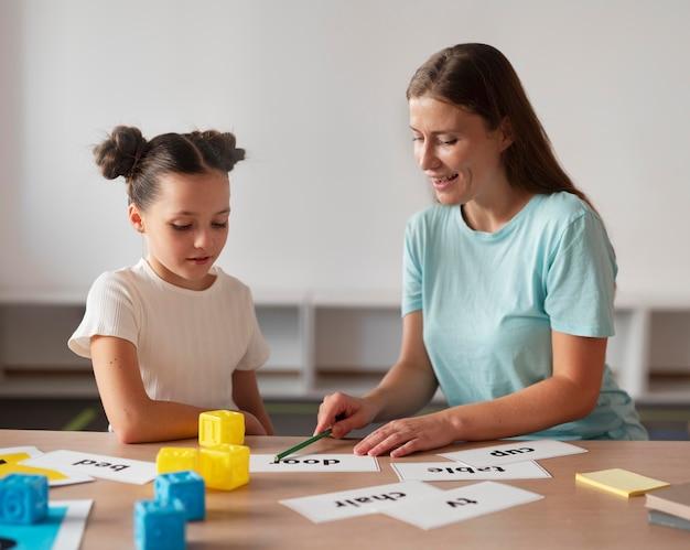 Psychologue aidant une petite fille en orthophonie