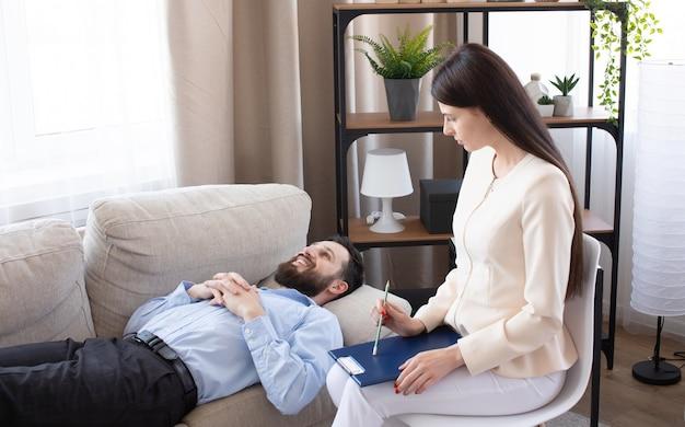 Psychologue ayant une séance avec son patient dans son cabinet de consultation privé.