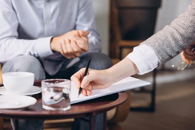 Psychologue ayant une session écoutant son patient prenant des notes donnant des conseils