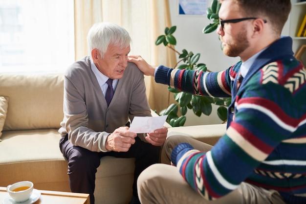 Psychologue consoling senior man