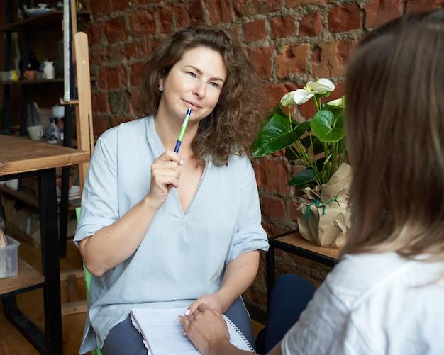 Psychologue féminine tenant la main de la femme, entraîneur écrivant au cahier.