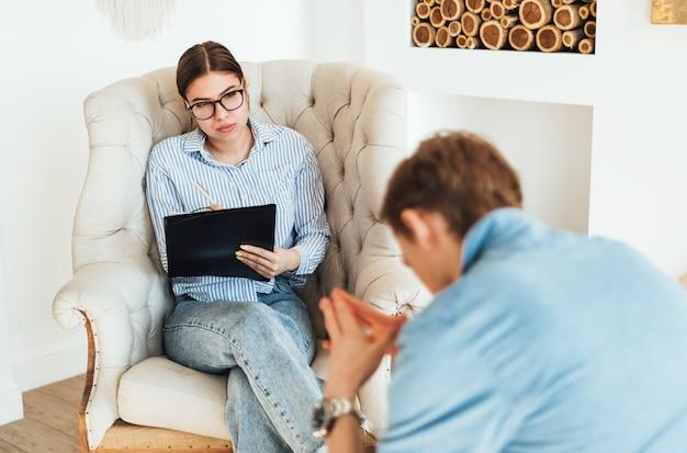 Psychologue femme caucasienne à lunettes assis sur une chaise menant une séance de psychothérapie avec un homme bouleversé du patient.