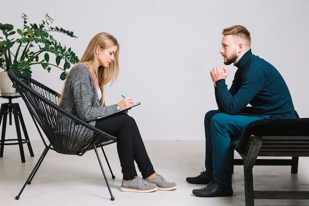 Psychologue femme écoutant un patient déprimé et écrivant des notes dans le presse-papiers