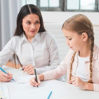 Psychologue femme regardant fille dessin au crayon de couleur