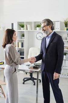 Psychologue mature réussie serrant la main d'une jeune cliente après consultation et décision de poursuivre leur coopération