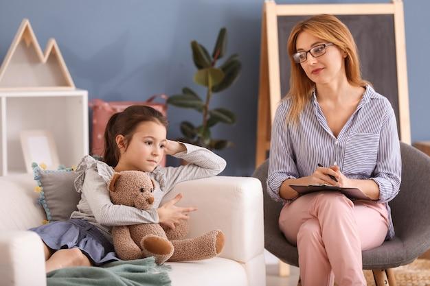 Psychologue travaillant avec une petite fille à l'intérieur