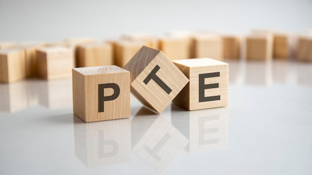 Pte - pearson tests of english acronyme concept sur cubes, fond gris. réflexion sur la surface réfléchissante de la table. mise au point sélective.