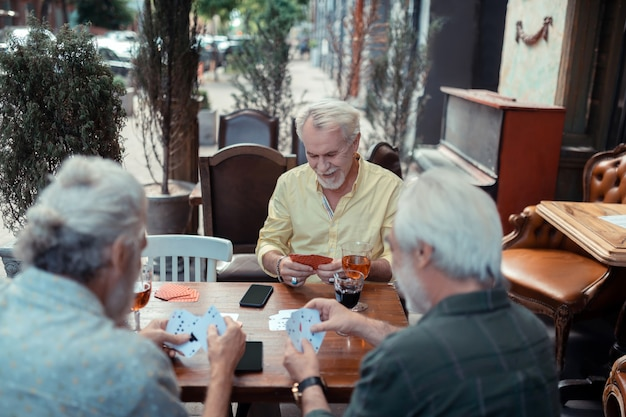 Pub extérieur. homme à la retraite aux cheveux gris se sentant bien assis à l'extérieur du pub et jouant aux cartes