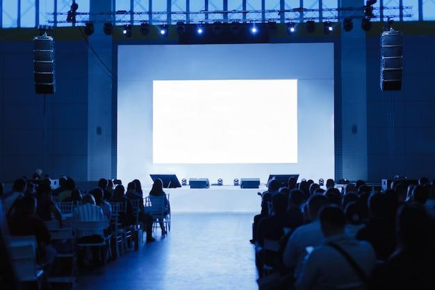 Public à la salle de conférence. se concentrer sur la scène. les gens attendent l'orateur. photo teintée bleu