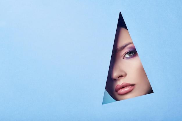 Publicité belles lèvres charnues de couleur rose vif yeux parfaits, femme regarde dans le papier de couleur bleu trou, salon de beauté. maquillage des yeux, publicité pour les soins du visage, lèvres parfaites, cosmétiques de beauté de mode