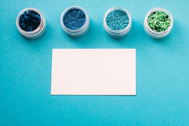 Publicité de maquilleur. fards à paupières et carte papier sur bleu