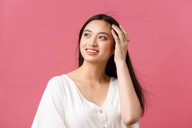 Publicité de produits de beauté, soins capillaires et concept de mode pour femmes. femme asiatique romantique sensuelle regardant loin avec un sourire rêveur tout en courant la main dans les cheveux, debout sur fond rose heureux.