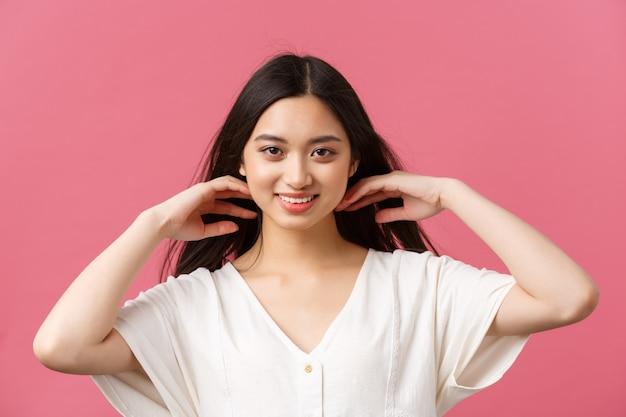 Publicité de produits de beauté, soins capillaires et concept de mode pour femmes. femme asiatique séduisante sensuelle et tendre montrant ses cheveux brillants et sa coupe de cheveux élégante après le salon de coiffure, fond rose.