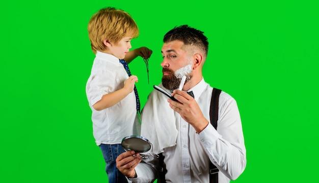 Publicité de salon de coiffure. fils et père au salon de coiffure. assistante de papa. fête des pères. rasage au salon de coiffure.